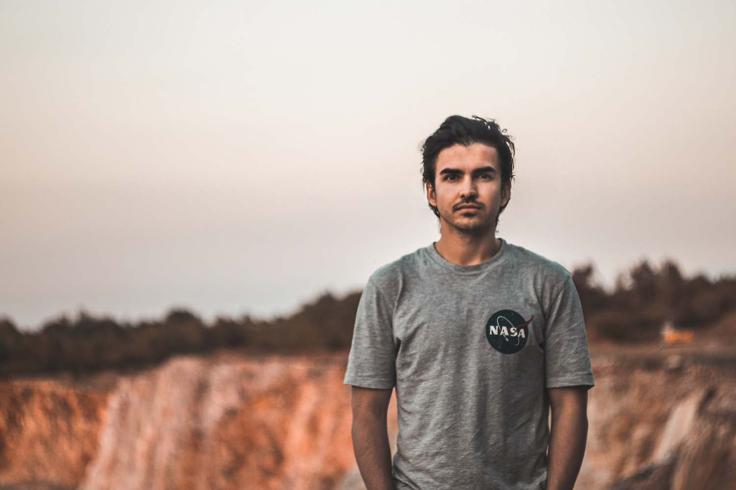 A guy in NASA t-shirt standing in a quarry.